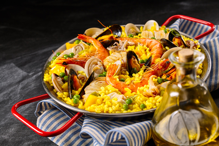 Traditional Spanish recipe for paella a la margarita with pink prawns, clams and mussels on yellow saffron rice with peas served with olive oil for a tasty seafood appetizer