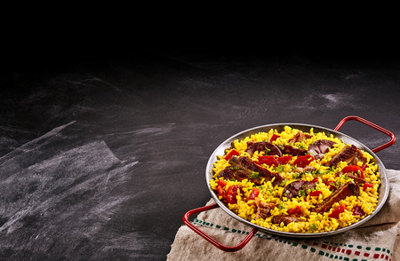 Serving of paella al homo with spare ribs and black pudding on yellow saffron rice flavored with red bell peppers and herbs in the corner of the frame over slate with plenty of copyspace for your menu
