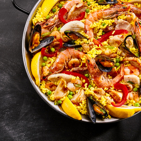 tangy: Serving of gourmet seafood paella with pink prawns, mussels, fish, peas, saffron rice and slices of tangy fresh lemon for flavoring in a metal dish, overhead view in square format Stock Photo