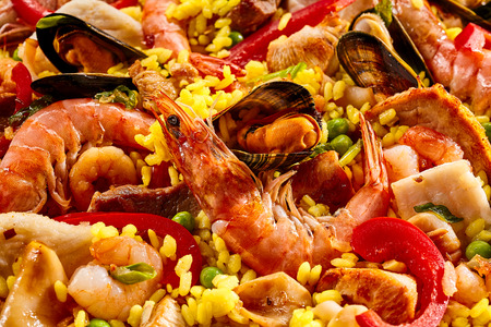 conceptional: Close up full frame background of delicious seafood paella with prawns and mussels in a bed of saffron rice and vegetables