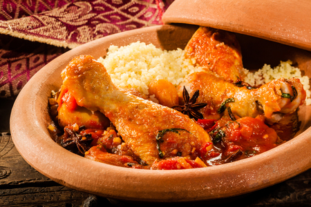 couscous: Close Up of Traditional Tajine Berber Dish Made with Chicken Legs, Couscous and Savory Tomato Sauce Served in Covered Clay Pottery Dish on Rustic Wooden Table with Napkin