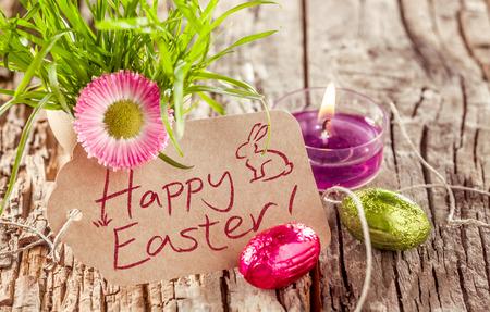 Fondo de Pascua feliz todavía la vida con una tarjeta escrita a mano rústico, la quema de velas, flores de primavera fragante y embalaje flexible de los huevos de chocolate