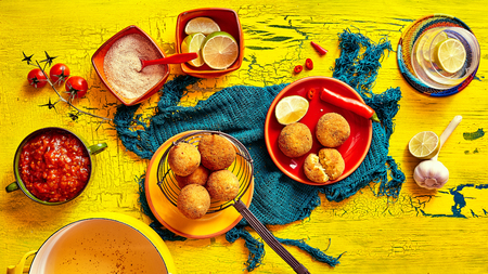 speciality: Brazilian speciality of bolhinos in frying basket and plates surrounded by lemons, tomatoes, dip and spoons Stock Photo