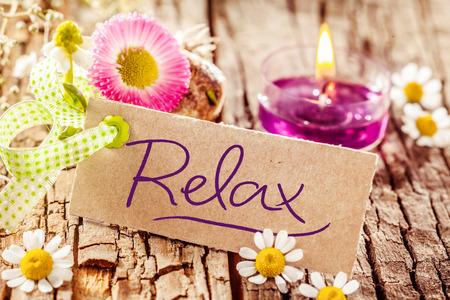 Leuke ontspanning scherm met handgeschreven ontspan teken ingesteld op boomschors oppervlak versierd met verschillende bloemen en kaarsen Stockfoto