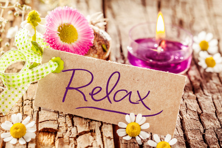 Cute relaxation display with handwritten relax sign set on tree bark surface decorated with various flowers and candle