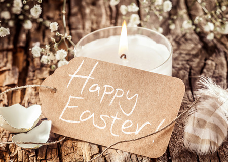 easter sign: Calm display of handwritten Happy Easter sign placed on tree bark decorated with white flowers, candle, feather and egg shells