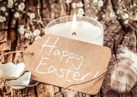 Kalm weergave van handgeschreven Happy Easter teken geplaatst op boomschors versierd met witte bloemen, kaars, veer en eierschalen