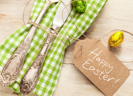Decorative fresh spring Easter table setting with a vintage silver knife and fork over a white and green checked napkin with a Happy Easter greeting on a gift tag and foil chocolate eggs