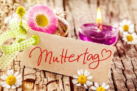 acknowledgment: Fresh spring or summer still life with flowers and a burning pink aromatic candle celebrating Muttertag or Mothers Day with a hand written greeting in German on a brown gift tag with a heart for love