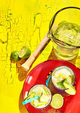 bebidas alcoh�licas: De arriba hacia abajo vista de bebidas alcoh�licas brasile�os caseros con rodajas de lim�n y pajitas sobre viejo fondo de madera desgastada Foto de archivo