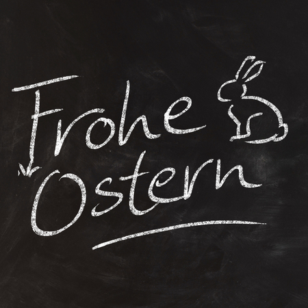 zeichen: Handwritten Frohe Ostern on black chalkboard fun with cute little rabbit for happy easter cards in germany