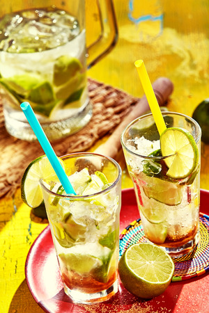 Tray with tall glass drinking cups filled with homemade caipirinhas and topped with limes and straws Stock Photo