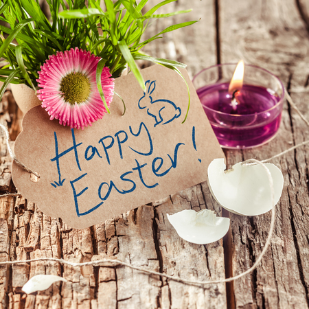 written: Handwritten Happy Easter wishes or greeting on a brown gift tag with a broken eggshell, fresh grass with a colorful spring flower and burning candle, rustic wood background Stock Photo