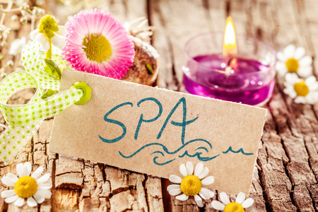 aromatherapy candle: Sweet smelling display of handwritten spa sign placed on tree bark adorned with flowers and aromatherapy candle