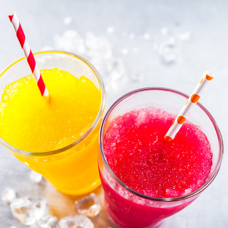 crushed ice: High Angle Still Life View of Refreshing and Colorful Frozen Fruit Slush Granita Drinks - Yellow and Red - in Glasses with Patterned Straws on Cold Metal Surface with Copy Space