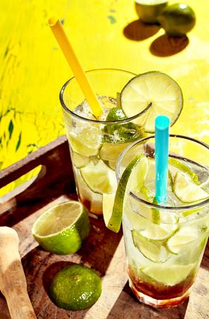 bebidas alcoh�licas: Dos vasos de bebidas alcoh�licas brasile�os caseros con rodajas de lim�n y pajitas sobre viejo fondo de madera desgastada en la bandeja de madera
