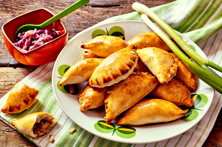 plateful: Close Up of Plateful of Fresh Baked Empanada Pastries with Fresh Green Onions and Cabbage Side Dish Served on Rustic Wooden Table with Copy Space