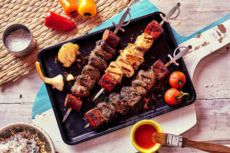 High Angle View of Variety of Grilled Meat Skewers Surrounded by Fresh Ingredients and Sauces and Served on Pan Placed on Rustic Wooden Paddle