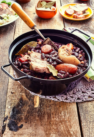 black bean: High Angle Close Up View of Traditional Brazilian Stew with Beans and Variety of Meats Served in Black Metal Pot on Doily and Rustic Wooden Table Surrounded with Garnishes