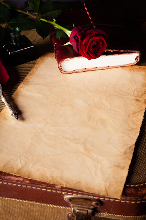 letter writing: Vintage aged discolored sheet of note paper for writing a love letter with a fountain pen and single red rose on a book, high angle, close up view with copy space on the note paper Stock Photo