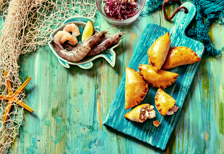 turnover: High Angle View of Baked Seafood Empanada Pastries Served on Blue Cutting Board and Surrounded by Fresh Ingredients on Nautical Themed Blue Painted Table with Fishing Net and Copy Space Stock Photo