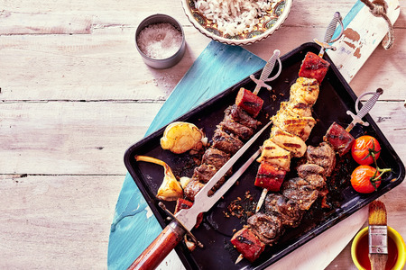 High Angle View of Variety of Grilled Meat Skewers Surrounded by Fresh Ingredients and Sauces and Served on Pan Placed on Rustic Wooden Paddle, Still Life with Copy Space Banco de Imagens