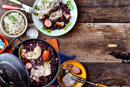 Vista elevada de la tradicional brasileña Bean y plato de carne Servido con placas laterales y Guarniciones en mesa de madera rústica, con copia espacio