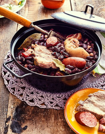 PULSE: High Angle Close Up View of Traditional Brazilian Stew with Beans and Variety of Meats Served in Black Metal Pot on Doily and Rustic Wooden Table Surrounded with Garnishes