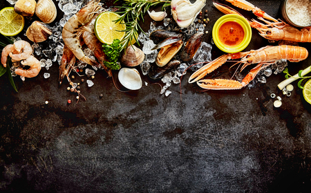 langouste: High Angle Seafood Cuisine Background Image with Fresh Shellfish - Shrimp, Langostino, Mussels and Clams - and Ingredients on Dark Background with Copy Space Stock Photo