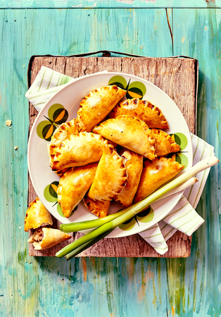 plateful: High Angle View of Plateful of Fresh Baked Empanada Pastries with Fresh Green Onions Served on Rustic Blue Painted Wooden Table