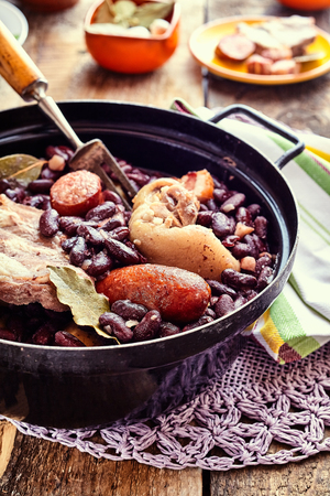 様々 なソーセージや繊細なドイリー、素朴な木製のテーブルに鋳鉄鍋に肉類と伝統的なブラジル豆のシチューのクローズ アップ