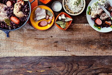 伝統的なブラジルのBeanと肉料理の高角ビューは、コピースペースと素朴な木製テーブルにサイドプレートとガーニッシュで提供 写真素材