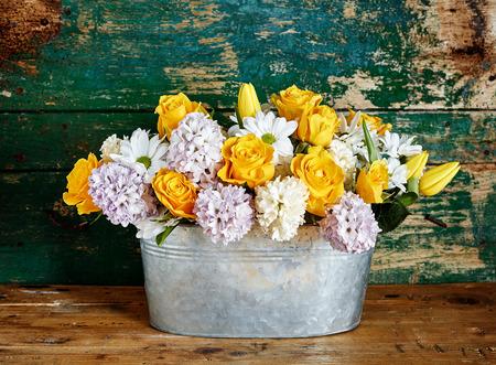 Rustieke bloemstuk gemaakt van gele rozen, madeliefjes, tulpen en hyacinten in een metalen emmer op een houten vloer met een groene gepelde muur achter Stockfoto