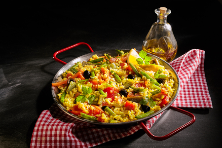 Healthy serving of paella verduras with asparagus in a traditional Spanish vegetarian recipe with red bell peppers, herbs and olives on a bed of yellow saffron rice served with an olive oil dressing