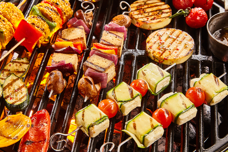 Assorted shish vegan or vegetarian kebabs with tofu and haloumi grilling on a grill over barbecue with colorful tomatoes and bell peppers, onion and eggplant for a tasty summer picnic