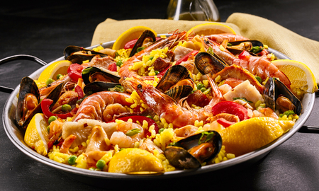 pan: Close up of homemade delicious paella a la margarita in frying pan with black handles on dark table Stock Photo