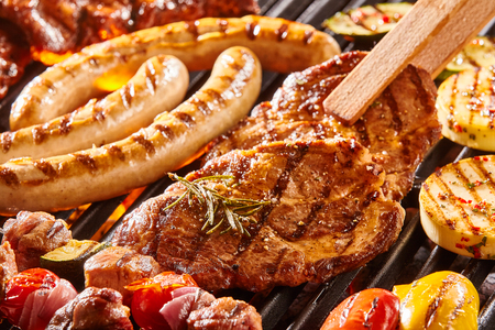 saucisse: Délicieux assortiment de viande cou steak et des légumes à griller sur un barbecue avec saucisses de porc, côtelettes, brochettes avec des brochettes mixtes, le poivron et l'aubergine dans une vue rapprochée avec des pinces tournant une côtelette Banque d'images