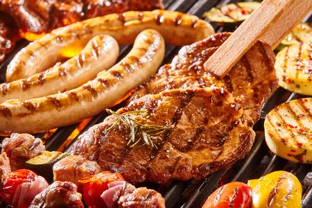 Köstliche Auswahl an Fleisch Nackensteak und Gemüse Grillen auf einem Grill mit Würstchen aus Schweinefleisch, Koteletts, Spieße mit gemischten Kebab, Paprika und Auberginen in einer Nahaufnahme Ansicht mit einer Zange ein Kotelett drehen