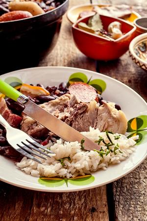 plato de comida: Picante tradicional guiso de Feijoada brasileña con costillas de cerdo, chorizo ??y frijoles negros servido en un plato con arroz y sabrosas para un plato nacional Foto de archivo