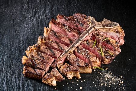 t bone: Grilled medium rare t-bone steak with seasoning sliced through to the bone in gourmet presentation on a slate background