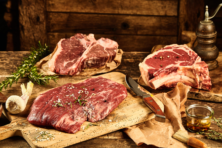 assorted: Old wooden table and chopping board covered with raw uncooked t-bone, rib tips and flank parts, cote de boeuf, beside seasonings, oil and rosemary