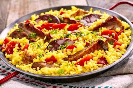 homo: Serving of speciality Spanish Al Homo paella with spare ribs and black pudding on savory rice with red peppers served in a metal dish