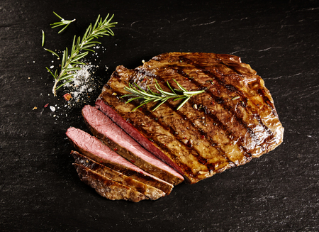 medium closeup: Single roasted medium rare sliced flank beef piece with rosemary over dark table background Stock Photo