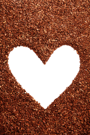 bark mulch: Pine bark mulch surrounding single white loving heart symbol with copy space for nature lovers Stock Photo