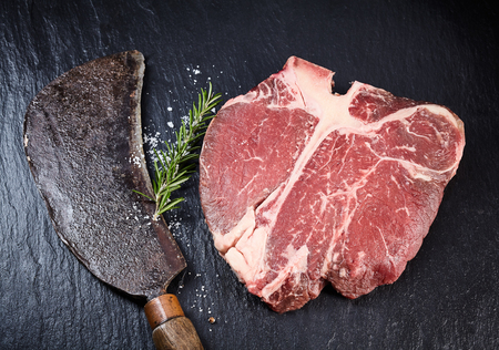 t bone: Lean matured raw t-bone steak and vintage cleaver with fresh rosemary on a slate background, overhead view