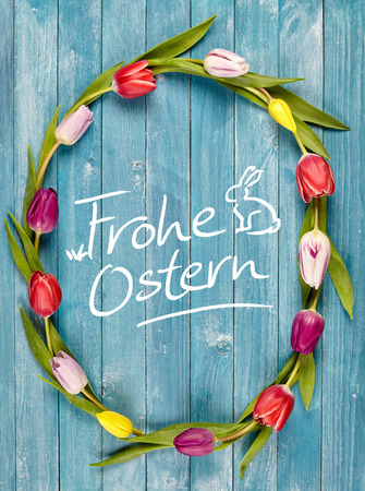 Ostern: Frohe Ostern, or Happy Easter, greeting card with a colorful fresh multicolored tulip wreath or frame surrounding the central handwritten German text with a cute Easter bunny Stock Photo