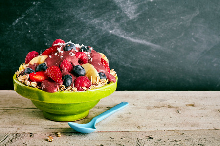 shreds: Nutritious large ceramic green bowl of oats, blueberries, bananas, strawberry and coconut shreds with blue spoon on wooden table with copy space