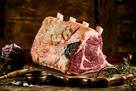 Single large piece of cote de boeuf meat with fat and rib bones with rosemary on top of wooden plate Stock Photo