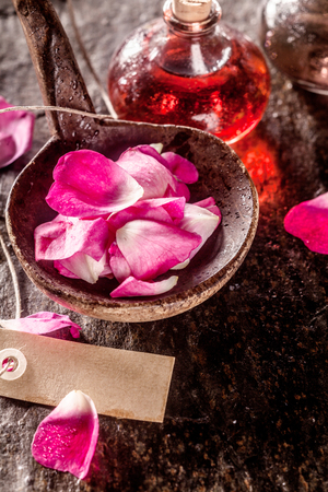 aromas: High Angle Spa Still Life of Rose Petals in Rustic Bowl on Table with Blank Paper Tag and Old Flasks Filled with Colorful Essential Aromatic Oils