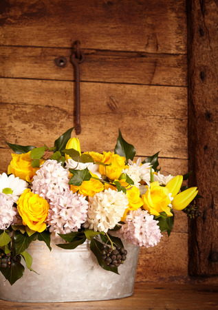galvanised: Group of beautiful white and yellow flowers in old galvanized steel bucket over rustic interior background Stock Photo